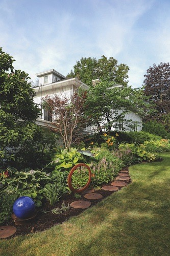 A variety of texture and color, as well as flowering perennials and bushy foliage, are what add to the artistry of Rashka's garden. This portion is mostly hostas, along with a magnolia tree, bloodgood Japanese maple, pink astilbe, ferns and yellow ligularia.
