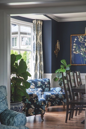 The family's dining room accommodates plenty of people at their Pottery Barn table that seats ten. The botanical sconce is by Visual Comfort and the Chinoiserie artwork is by Ballard Designs.