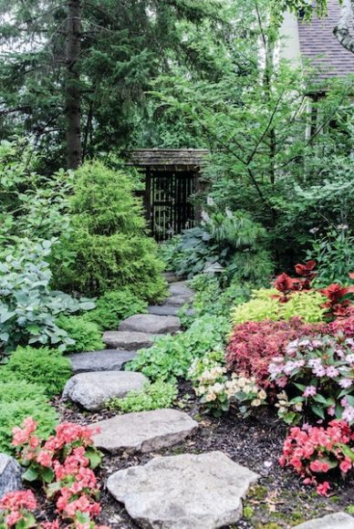 The stone pathway leads from the front yard to the backyard and is flanked by flowering plants, including coleus and Solenia begonia.