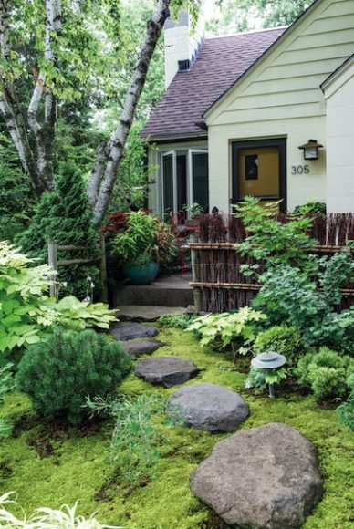 Moss and stone steps lead from the sidewalk to the front of the Mathews' home. Surrounding the path include sun king aralia, dwarf mugo pine, a Japanese maple and a dwarf ginkgo tree. The fence is called a broom fence and is fashioned from 900 willow branches