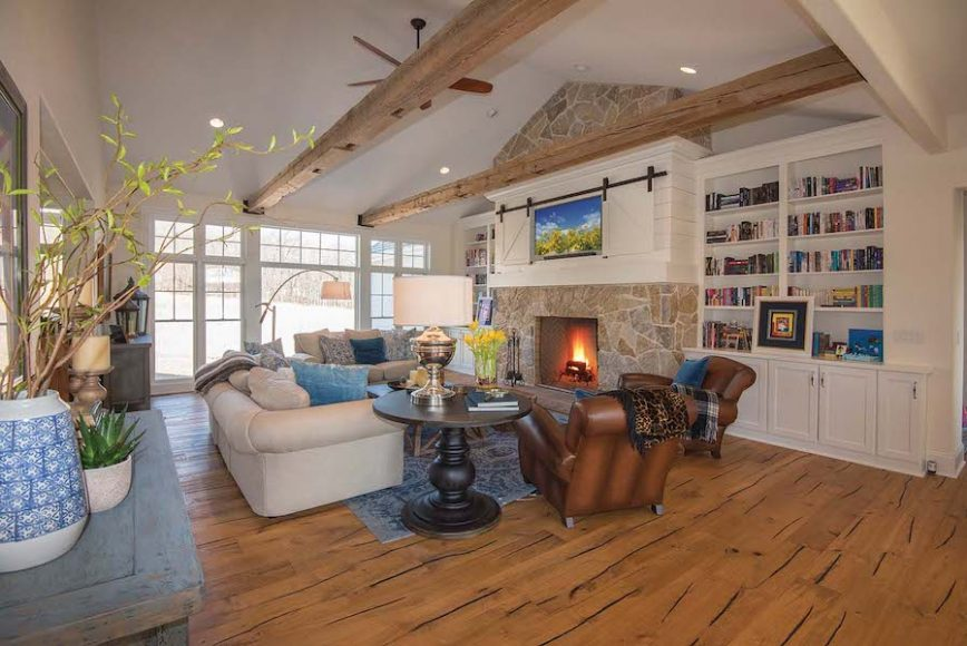 A cozy custom home design has no shortage of visual appeal with its stone-face fireplace and rustic ceiling beam details.
