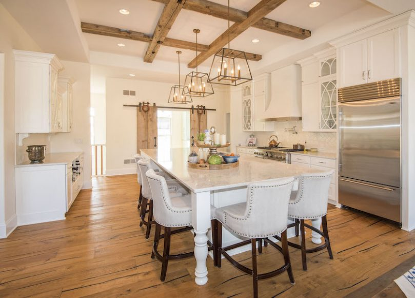 Warmth is added to this custom kitchen with the use of rustic beams and sliding barn doors. The mixed materials offer a clean and timeless look.