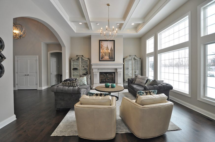 Conversation takes center stage in the living room of this custom home. Coffered ceilings and arched entrances bring grandeur to this Midwest home.